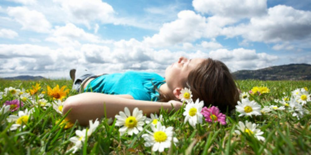 A girl relaxing and enjoying hypnosis on a beautiful day
