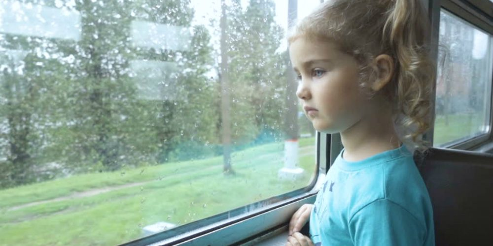 A child looks out the window of a train while in hypnosis