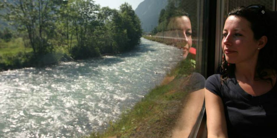 A woman looks out the window of a train while in hypnosis